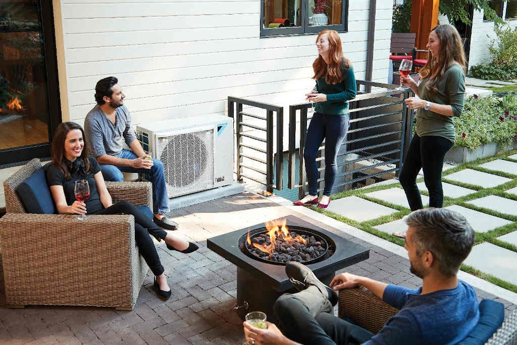 people enjoying patio with DAIKIN FIT heat pump in background